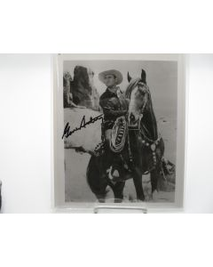 "8x10 signed black and white photograph of Gene Autry, ""America's favorite singing cowboy"", on horseback."